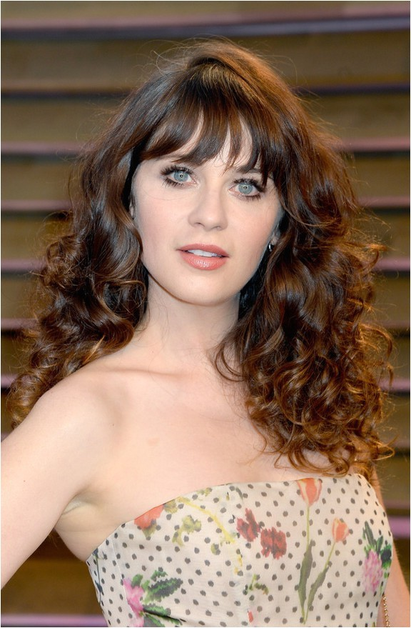 zooey deschanel long curly hairstyle with wispy bangs