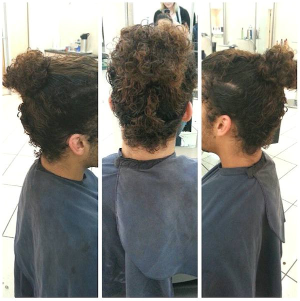 A picture of a curly haired guy ting a haircut for his curly manbun hairstyle at