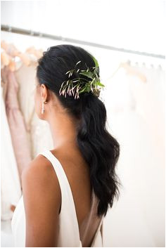 A low ponytail with texture and fresh florals make for a beautiful wedding day hairstyle