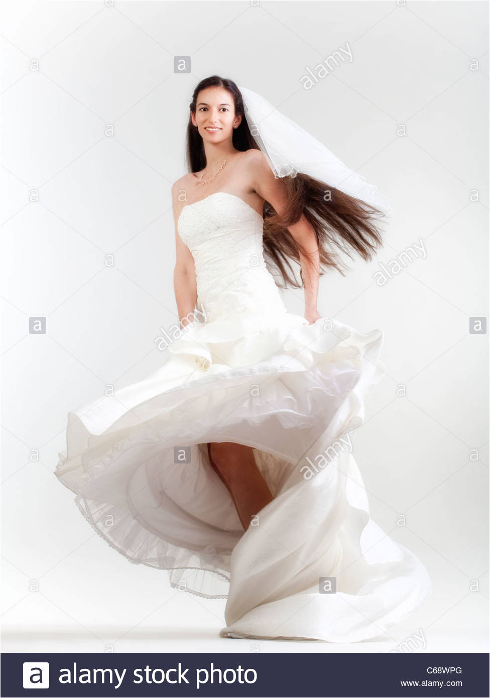 portrait od a bride with long dark hair in wedding dress isolated on gray