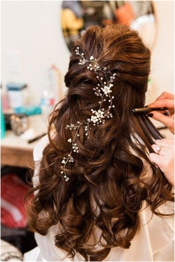 Ashely wore her hair pulled half back in loose romantic curls accessorized with a crystal hairpiece Venue CW Hill Country Ranch Event Planner Kristine