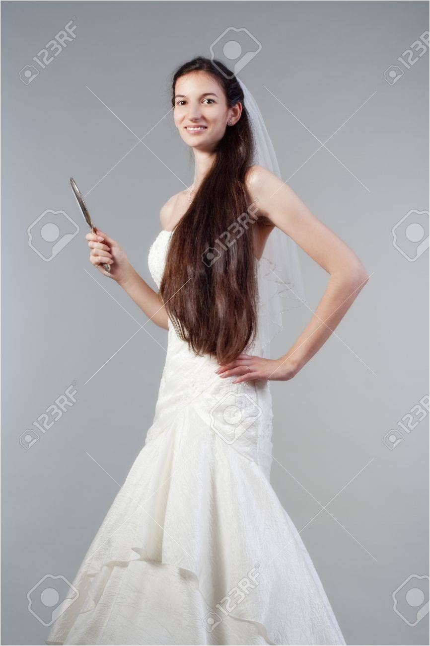 portrait od a bride with long dark hair in wedding dress isolated on gray Stock