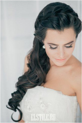 A long tousled hairstyle with a braided crown and a side swept gathering of romantic waves