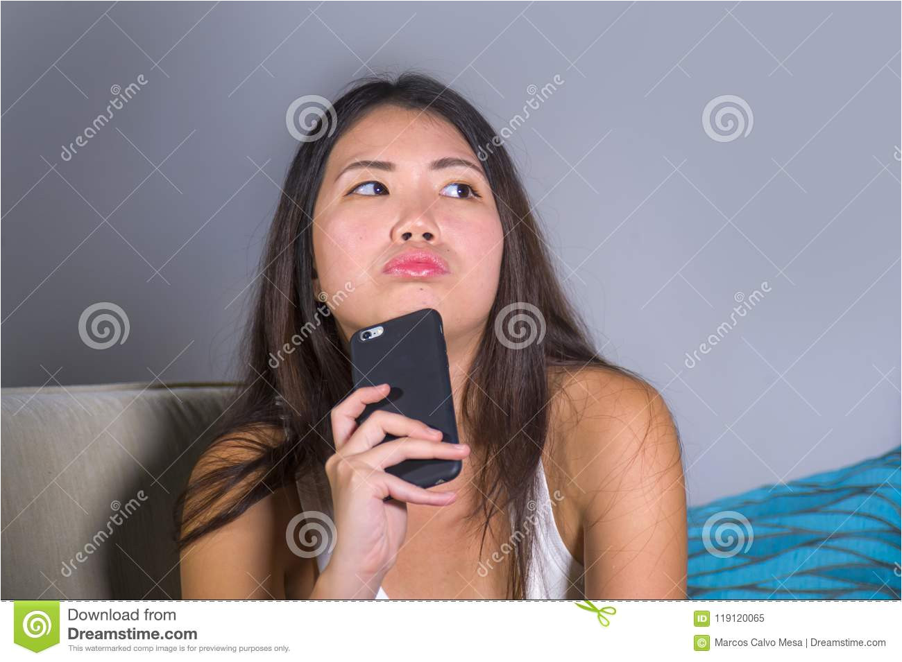 Young sweet happy and pretty Asian Korean girl using internet social media app on mobile phone