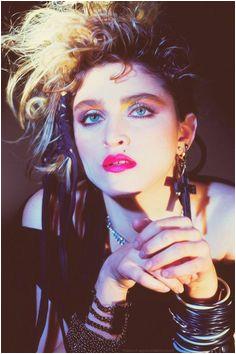 80er Kleidung Madonna im Punk Outfit mit schwarzer schulterfreien Bluse vielen Armbändern und riesigen Accessoires