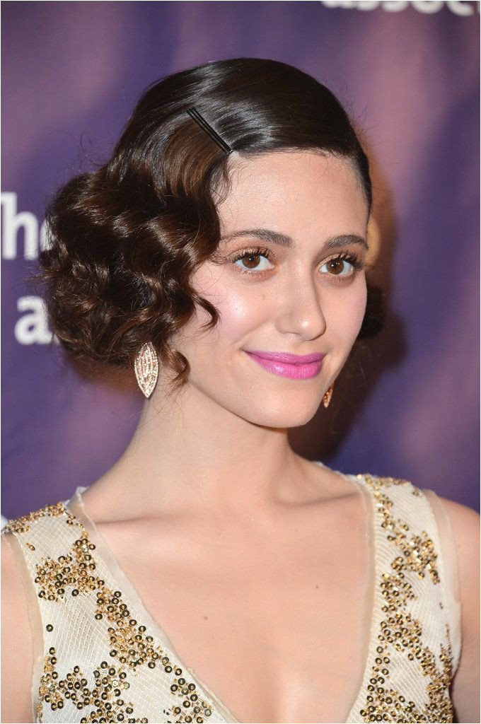A bobby pin snuck right above a bevy of curls just as Emmy Rossum styled her waves in March is a modern twist on a classic Gatsby look